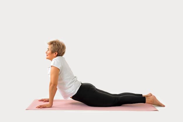 Elegante mulher idosa fazendo ioga em um fundo branco