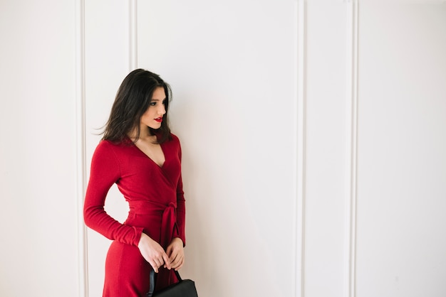 Elegante, mulher jovem, em, vestido vermelho, com, bolsa, em, sala