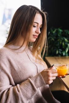 Elegante, mulher jovem, xícara segurando, de, bebida, em, barra, contador, em, café