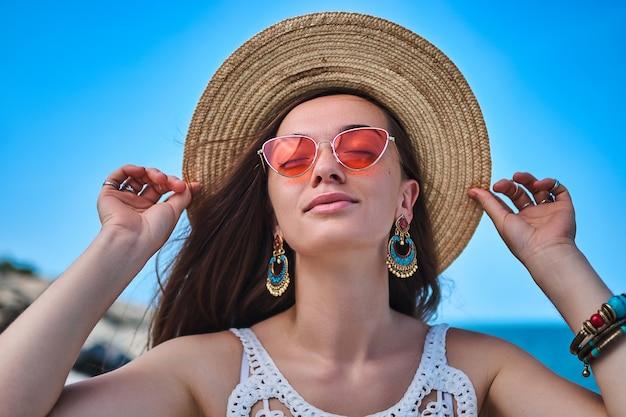 Elegante mulher morena atraente, com os olhos fechados, vestindo um chapéu de palha, brincos grandes e óculos vermelhos, aproveitando o verão