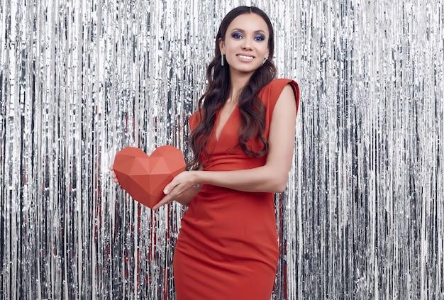Elegante mulher morena hispânica no luxuoso vestido vermelho mantém um coração de papel