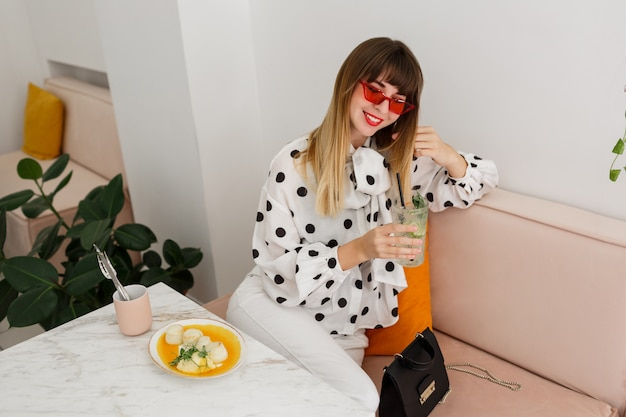Elegante mulher morena sentada no café e beber cocktails