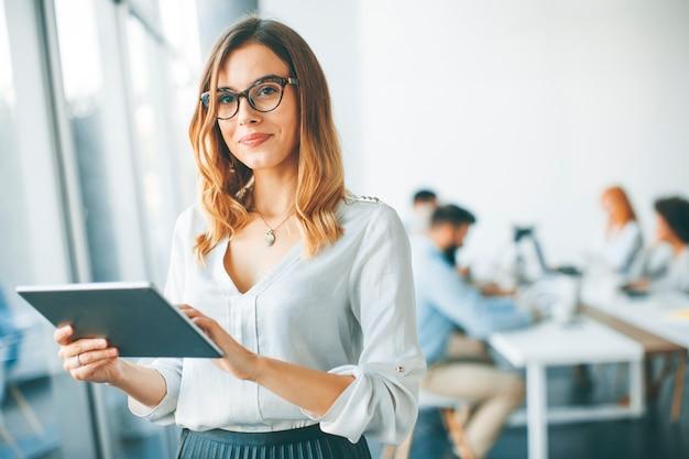 Elegante, mulher negócios fica, em, escritório, com, tablete digital
