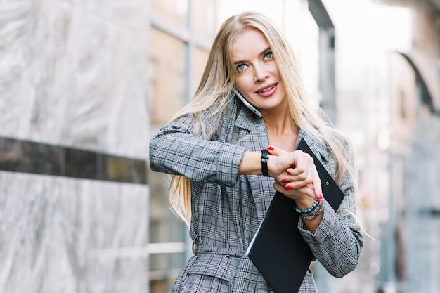 Elegante, mulher negócios, olhar, relógio
