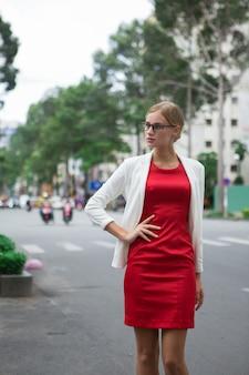 Elegante mulher nova séria no vestido vermelho na rua