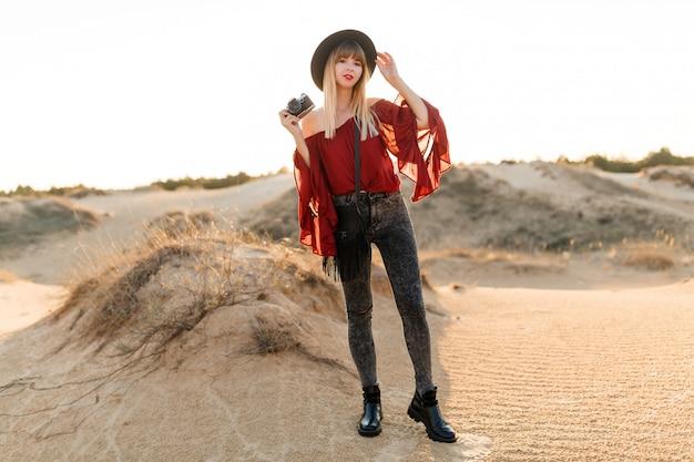 Elegante mulher posando no deserto, vestindo roupa de chapéu preto e boho