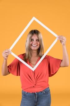 Elegante mulher segurando a moldura de foto de borda branca na frente de seu rosto
