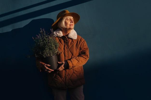 Elegante mulher sênior com planta em vaso. idosa segurando um vaso de flores com plantas de lavanda