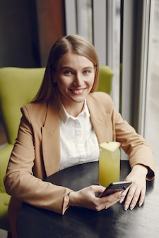 Elegante mulher sentada à mesa com cocktail e telefone