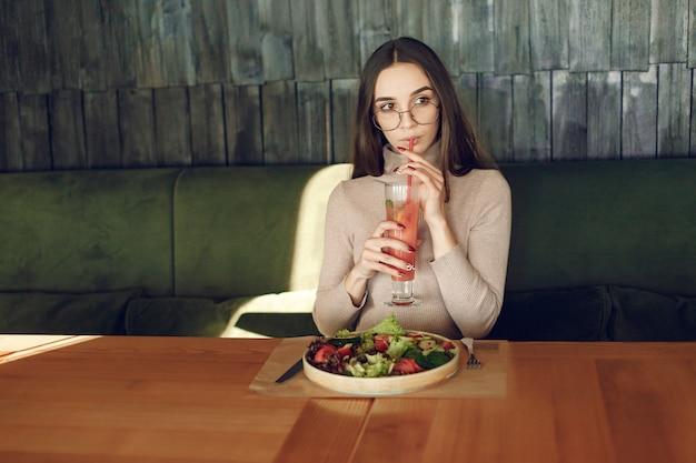 Elegante mulher sentada à mesa com coquetel e salada