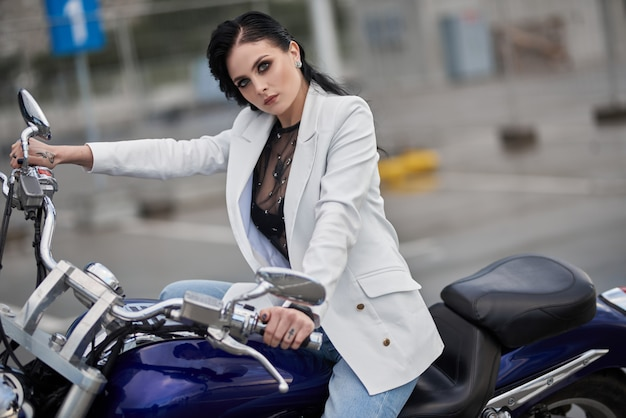 Elegante mulher sentada em uma motocicleta estacionada perto de um shopping center.