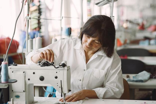 Elegante mulher sentada no estúdio e costurar pano