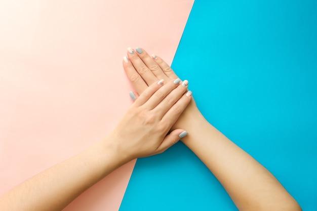 Elegante na moda geométrica com listras femininas manicure. mãos de mulher jovem bonita
