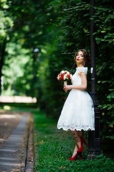 Elegante noiva e noivo posando juntos ao ar livre no dia do casamento