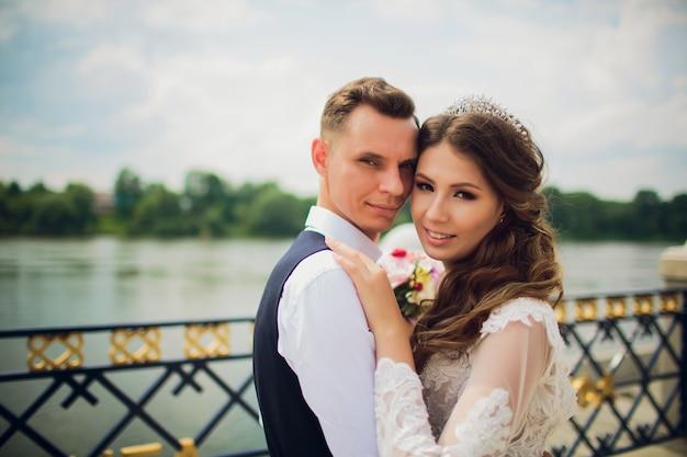 Elegante noiva e noivo posando no fundo do rio.