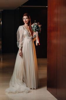 Elegante noiva ruiva em um vestido com mangas e buquê no interior.