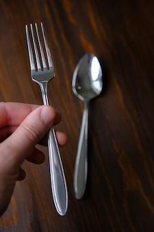 Elegante novo garfo na mão do homem