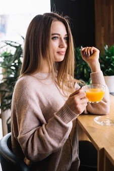 Elegante, positivo, mulher jovem, segurando, copo bebida, em, barra, contador, em, café