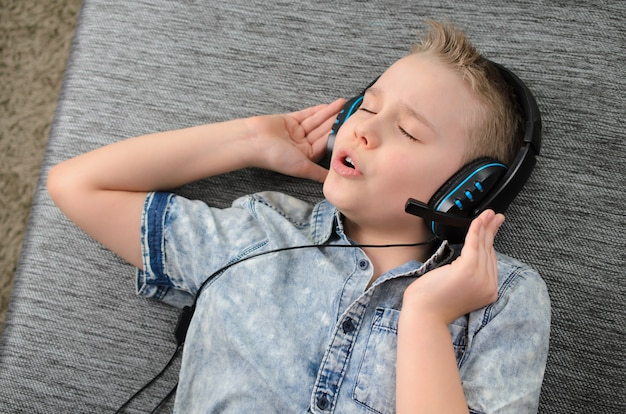 Elegante rapaz adolescente ouvindo música em fones de ouvido e cantando em casa feliz rapaz sorridente, descansando no ...