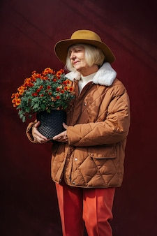 Elegante senhora sênior com vaso de flores. conteúdo feminino idosa carregando vaso com flores desabrochando