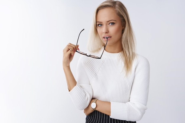 Elegante sensual mulher loira europeia em elegante camisola mordendo moldura de óculos e olhando glamour com um olhar sonhador para a câmera posando contra um fundo branco usando habilidades de sedução.