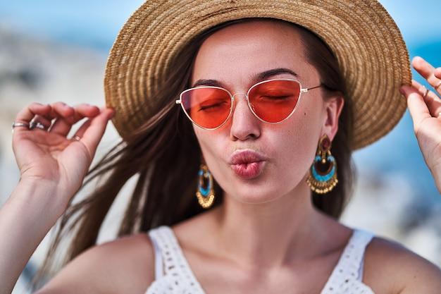 Elegante sensual mulher morena brilhante com os olhos fechados, vestindo um chapéu de palha, brincos grandes e óculos vermelhos, aproveitando o verão e soprando beijo de ar