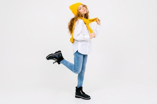 Elegante, sonha atraente garota caucasiana em uma camisa branca e calça jeans azul e um chapéu amarelo em botas posando com uma perna levantada no estúdio branco comprimento total, com espaço de cópia