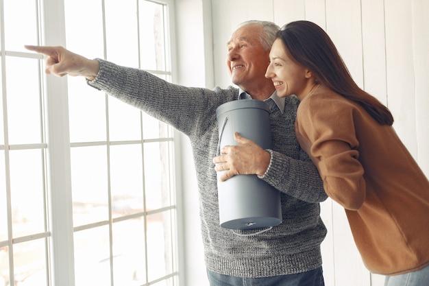 Elegante velho em pé em casa com a neta