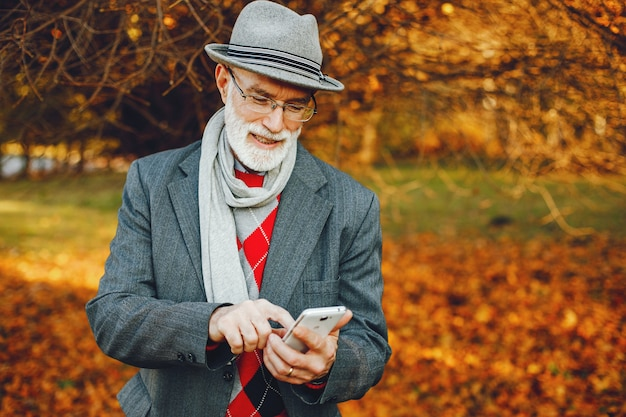 Elegante velho em um parque ensolarado de outono
