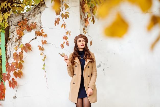 Elegante vestido com casaco bege, vestido azul escuro e boina marrom ao ar livre no outono