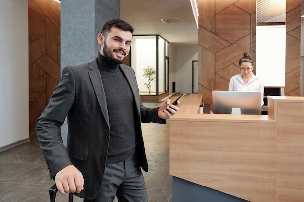 Elegante viajante de negócios com mala e smartphone em pé na recepcionista de trabalho do saguão do hotel