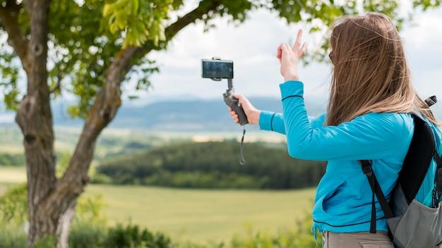 Elegante viajante tomando uma selfie ao ar livre