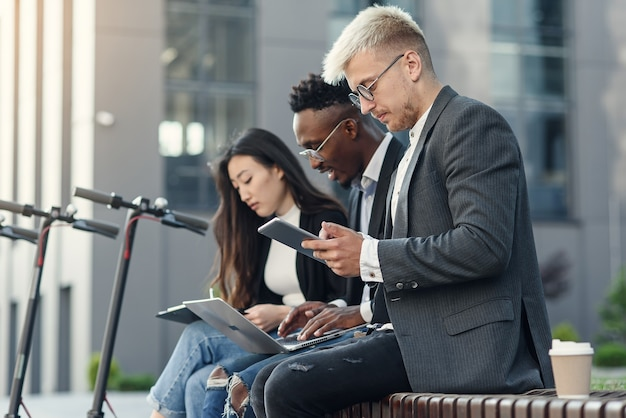 Elegantes colegas multirraciais sentados no banco perto do escritório discutindo assuntos de negócios