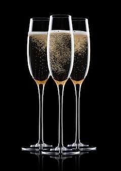 Elegantes copos de champanhe amarelo com bolhas no fundo preto com reflexão