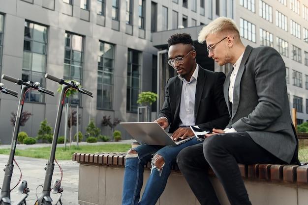 Elegantes dois colegas multirraciais do sexo masculino, sentados no banco perto do escritório e discutindo assuntos de negócios ao ar livre.