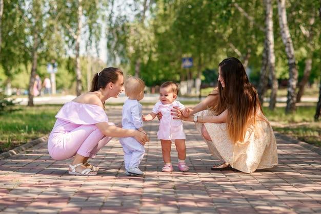 Elegantes jovens mães andando no parque urbano com suas filhas. lindas meninas estão brincando uns com os outros.