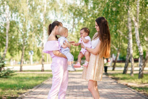 Elegantes jovens mães andando no parque urbano com suas filhas. womans lindo bebê estão brincando uns com os outros.