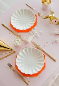Elegantes pratos brancos com talheres de ouro na mesa de aniversário preparada para menina. festa nas cores rosa, ouro e vermelho. decoração de festa de galinha. vista do topo