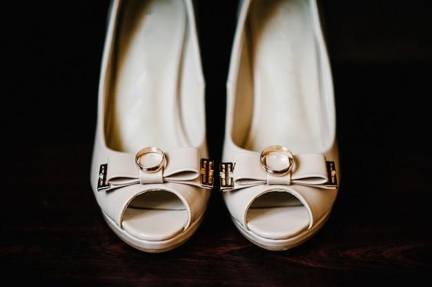 Elegantes sapatos brancos lacados, anéis de ouro são isolados em pé sobre fundo marrom.