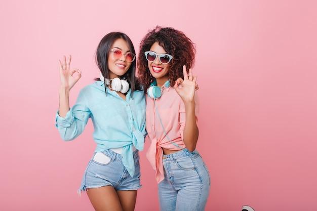 Elegantes senhoras americanas em trajes de verão, posando com um sorriso feliz. mulher caucasiana glamorosa com penteado brilhante, aproveitando o tempo livre com a amiga africana.