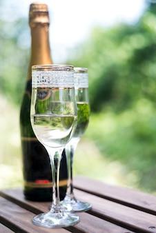 Elegantes taças de champanhe com garrafa de champanhe na mesa de madeira