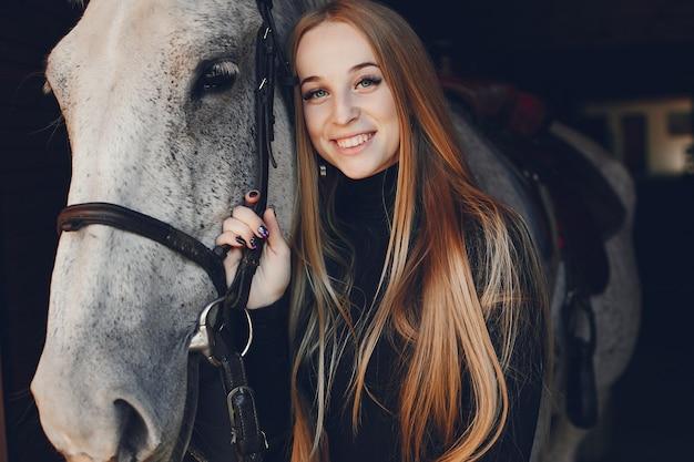 Elegants menina com um cavalo em uma fazenda