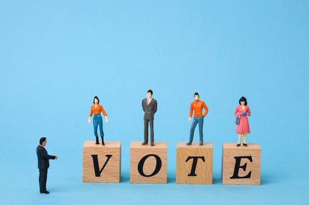 Eleitores em miniatura em cubos de madeira com a palavra voto