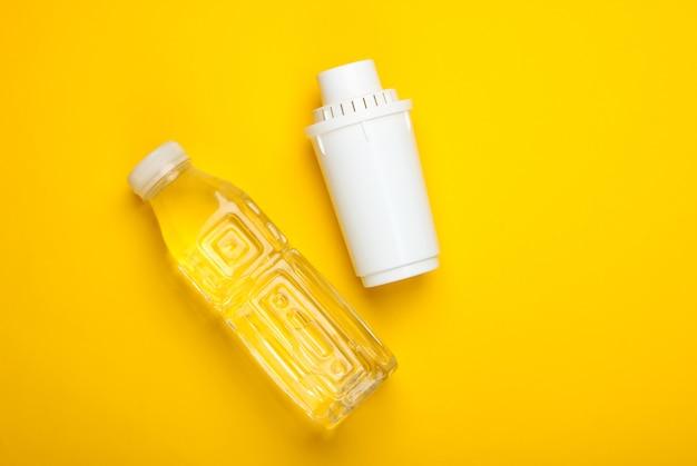 Elemento de filtro de purificador de água e garrafa de água pura em fundo amarelo. vista do topo