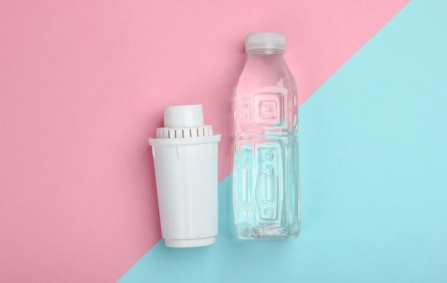 Elemento de filtro de purificador de água e garrafa de água pura em fundo azul rosa. vista do topo