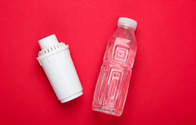 Elemento de filtro de purificador de água e garrafa de água pura sobre fundo vermelho. vista do topo