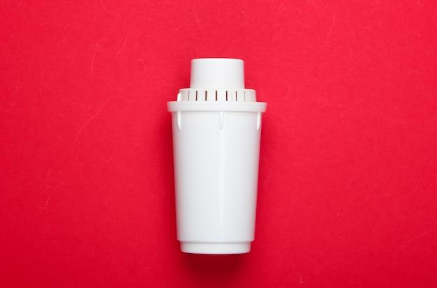 Elemento de filtro do purificador de água sobre fundo vermelho. vista do topo
