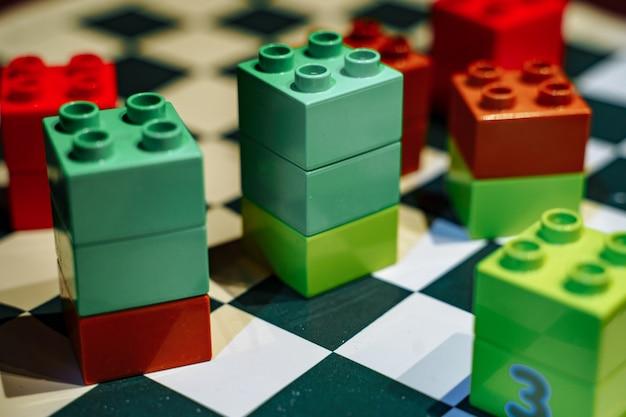 Elementos coloridos de peças infantis no tabuleiro de xadrez