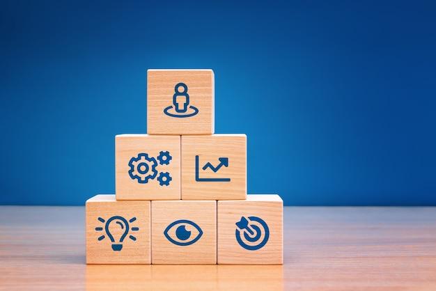 Elementos com estratégia de negócios de ícone e plano de ação no bloco de madeira. copie o espaço.