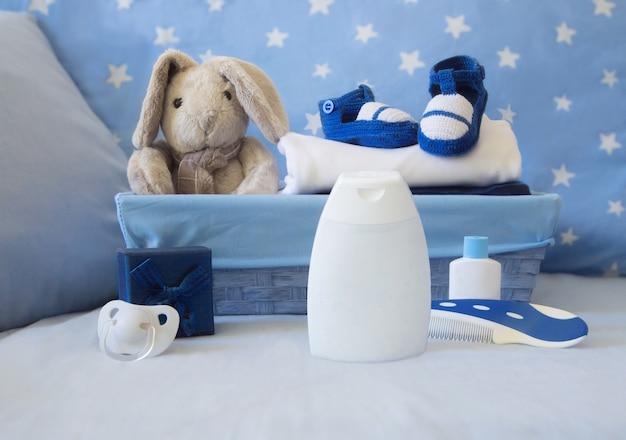 Elementos de bebê com cesta azul e sapatinhos
